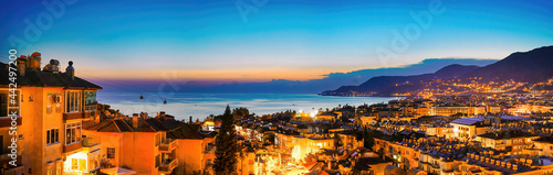 Obraz na płótnie Wide-format image of Turkish resort of Alanya - beautiful evening sky with reflection in water of bay, silhouette of mountains with scattering of lights and bright evening city, aerial photo