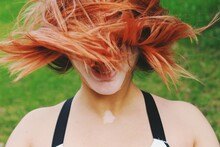 Portrait Of A Young Woman With Pink/orange Hairdoing A Hairwhip