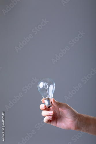 Close up of caucasian businesswoman holding light bulb, isolated on grey background