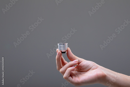 Close up of caucasian businesswoman holding base of light bulb, isolated on grey background
