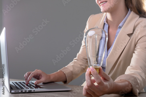 Smiling caucasian businesswoman holding light bulb using laptop, isolated on grey background