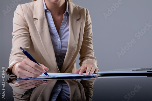 Midsection of caucasian businesswoman using laptop and taking notes, isolated on grey background