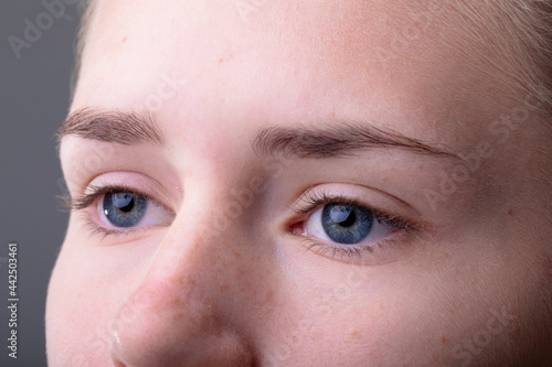 Close up of blue eyes of caucasian businesswoman isolated on grey background