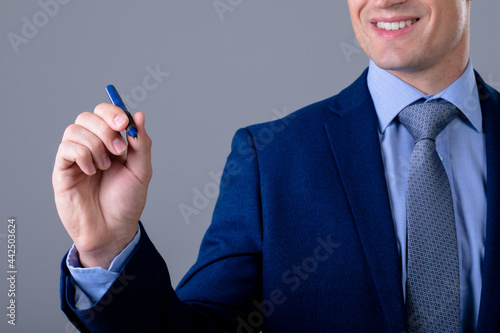 Smiling caucasian businessman holding pen, isolated on grey background