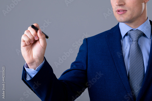 Midsection of caucasian businessman holding pen, isolated on grey background