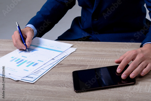 Midsection of caucasian businessman using smartphone and taking notes, isolated on grey background