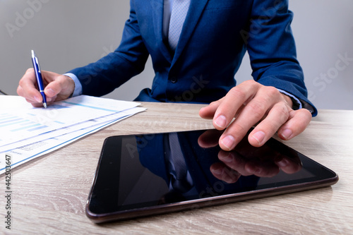Midsection of caucasian businessman using tablet and taking notes, isolated on grey background