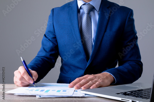 Midsection of caucasian businessman using laptop and taking notes, isolated on grey background