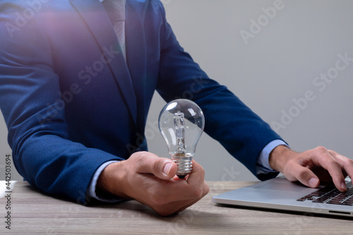 Midsection of caucasian businessman holding light bulb using laptop, isolated on grey background