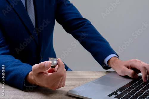 Midsection of caucasian businessman holding base of light bulb, isolated on grey background