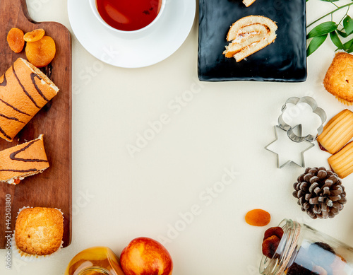 Billede på lærred top view of roll cake served with a cup of tea and cookies with cookie cutters a