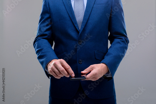 Midsection of caucasian businessman using smartphone, isolated on grey background