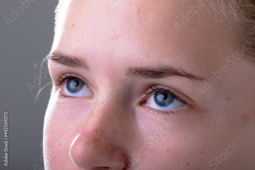 Close up of blue eyes of caucasian businesswoman, isolated on grey background