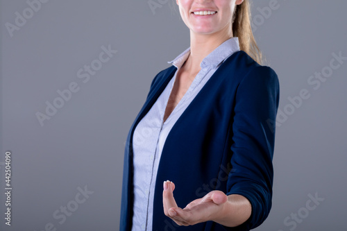 Smiling caucasian businesswoman reaching with her hand, isolated on grey background