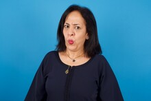 Middle Aged Arab Woman Standing Against Blue Background Expressing Disgust, Unwillingness, Disregard Having Tensive Look Frowning Face, Looking Indignant With Something.