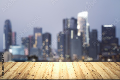 Table top made of wooden dies with blurry city view at dusk on background, templ Fototapet