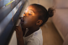 Surprised African American Girl Standing And Peering Through Window Blinds On A Sunny Day