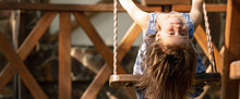 Portrait Of Beautiful Young Girl Sitting On The Swing Upside Down.  Copy Space For Design