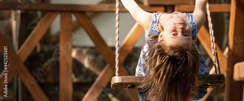 Billede på lærred Portrait of beautiful young girl sitting on the swing upside down