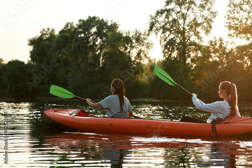 Fotografie, Obraz Two active young women, best friends kayaking in a lake surrounded by beautiful