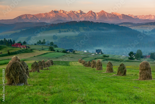 Fototapeta Rural Countryside with Haystack and High Tatra Mountains at Sunrise in Pieniny P