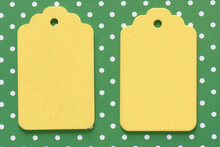 Two Retro Wooden Pastel Yellow Merchandise Tags Or Labels Isolated On White And Green Polka Dot Patterned Paper Background