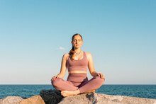 Woman Practicing Yoga In Lotus Pose On Beach
