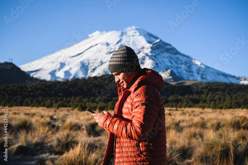 Cheerful traveler browsing phone against mountains