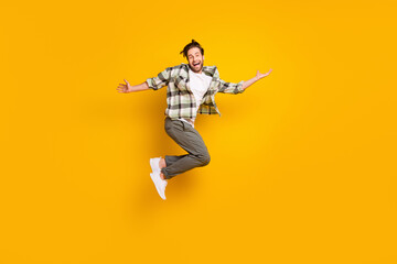 Full length photo of cheerful happy man jump up raise hands good mood smile isolated on yellow color background