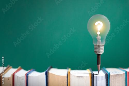 Lamp bulb on pencil  on book idea concept.