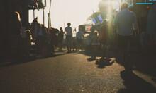 People Walk Down The Street In Summer. Blurred Shot.