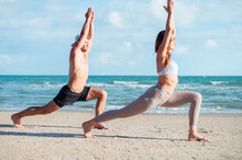 Young Couple Practicing Yoga On Beach At Sunrise Or Morning