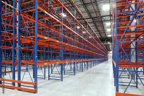 Fototapeta Tall steel blue and orange storage racks in empty storage industrial warehouse b