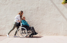 Woman Walking With Aged Mother In Wheelchair In Street