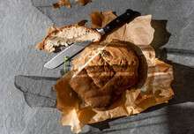 Homemade Bread With Knife On Parchment