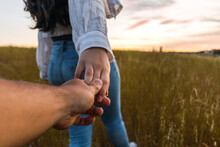 Couple Holding Hands In A Field With A Beautiful Sunset