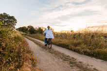 Back View Of A Blonde Woman On A Bike In A Field During Sunset