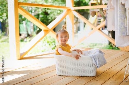 Tela cute caucasian toddler girl in a basket with clean linen on the veranda, hangs u