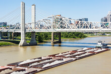 A Tugboat Pushing Barges Filled With Sand And Gravel Under The Interstate 65 Bridge In Downtown Louisville, Kentucky