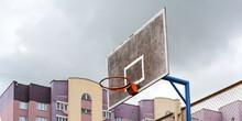 Orange Metal Basketball Hoop On Blue Support At Grid Fence