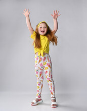 Happy Overjoyed Little Red-haired Girl Child Wearing Summer Fashion Outfit Rejoicing With Raised Hands Showing Happiness And Satisfaction Emotion Having Fun Standing Over Studio Wall Background
