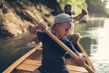 Boy Learning To Paddle Canoe With His Dad