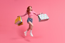 Joyous Trendy Stylish Carefree Woman Rejoicing With Sales, Shopping Time, Isolated On Pink Studio Background, Wearing Casual Outfit, Denim Jeans And Pink Shirt. Portrait Of Jumping Lady With Red Hair