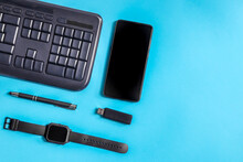 Keyboard, Smartphone And Wrist Watch. The Keyboard, Smartphone, Wrist Watch And Flash Drive Lie On The Left Against A Blue Background With Space For Text On The Right, Close-up Top View.