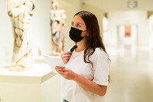 Attentive Visitor Girl In A Protective Mask, Who Is In The Museum During The Pandemic With An Information Booklet, ..looks At The Exhibits