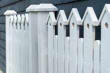 A White Wooden Fence With Two Gate Posts In The Center. The Top Of The Fence Has A Small Decorative Birdhouse With A Hole On The Top Of Each Paling.  There's A Navy Blue House In The Background.
