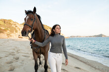 Smiling Woman Walking With Horse Against Sea