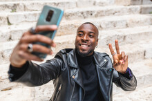 Cheerful Black Man Taking Selfie On City Stairs