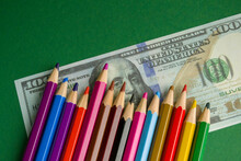 Multicolored Pencils On Souvenir Dollar Bills. Items Lie On A Green Background