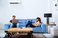 Young Couple Spending Free Time With Gadgets In Modern Living Room